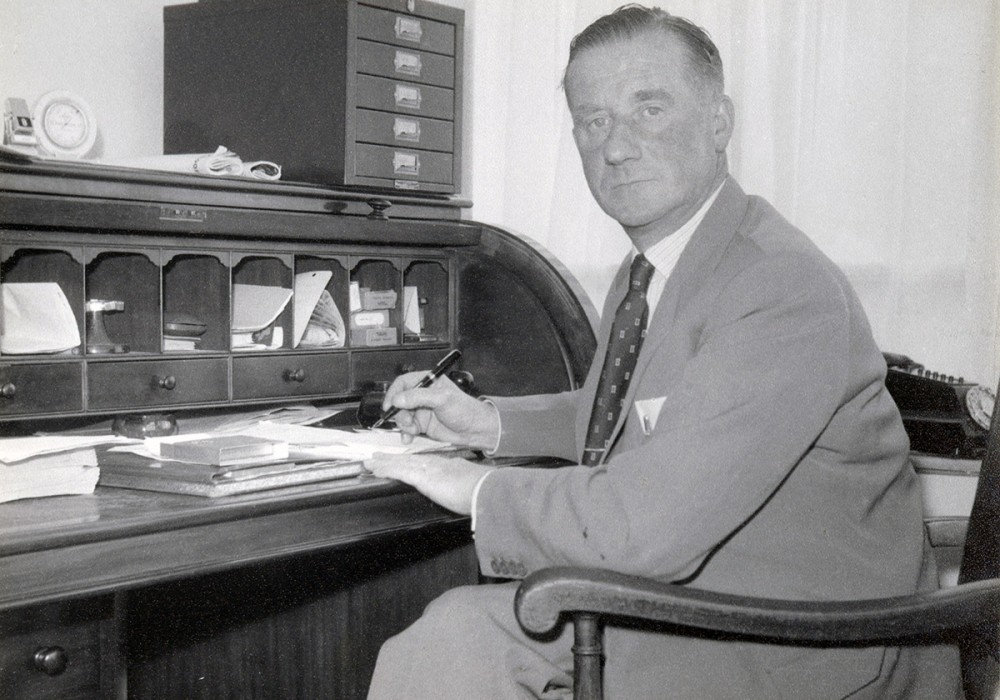 Ivor Dewdney working at his desk